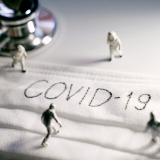 Miniature people doctors with protective suit prevention of pandemic Covid-19 and Coronavirus, surgical mask with Covid-19 text written on it with stethoscope, dramatic toned
